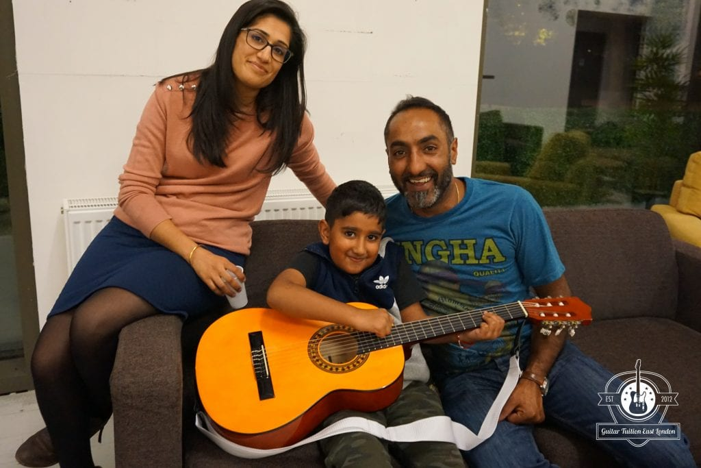 Kid with parents in guitar lesson