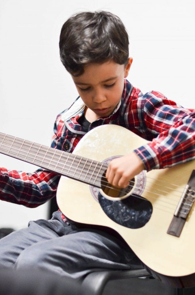 Child learning guitar with Guitar Tuition East London