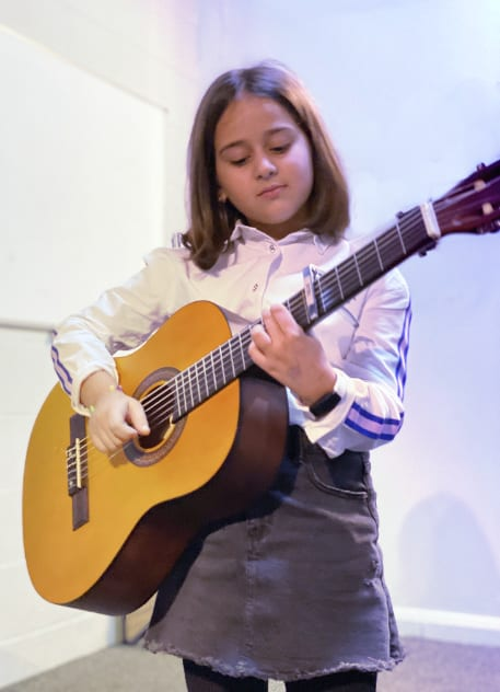 Student learning kids guitar with guitar tuition east london